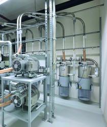 Zentrale Vakuumerzeugerstation mit Seitenkanalverdichtern und Sicherheitsfiltern im Hintergrund
